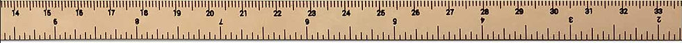 A classic wooden ruler or measuring stick horizontally spans the page.