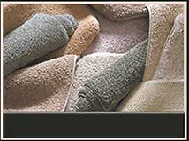 Rolls of plush carpet in pastel tones.