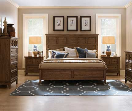 A photograph of a mission style bedroom suite, headboard, footboard, chest, dresser and two night stands in a sunny room with a wood floor and area rug.