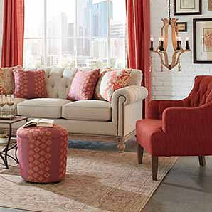 A sunlit living room scene with bright red accented Craftmaster sofa, chair and ottoman.