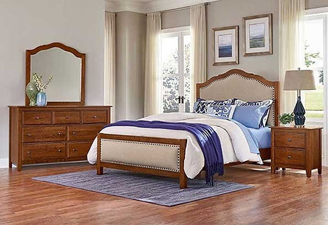 A photo of a medium finished Vaughan-Bassett bedroom suite, dresser, mirror, bed and nightstand on a wood floor