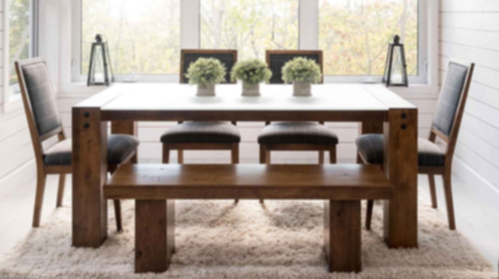 A Canadel furniture table, side chairs and bench in a sunlit room with shaggy rug