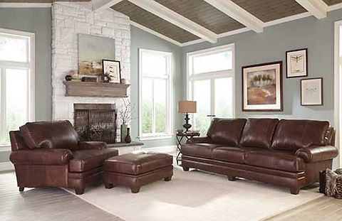 A sunny room scene with pale blue walls and brown leather sofa, chair and ottoman by Smith Brothers furniture