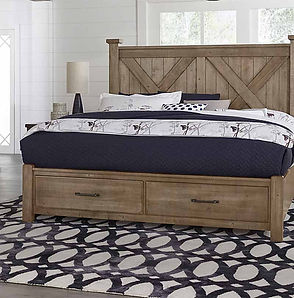 A sunlit room scene with a Vaughan-Bassett headboard, footboard and rails with navy blue bedding and geometric designer rug.