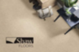 A top down photo of textured tan carpet with a Shaw Floors logo