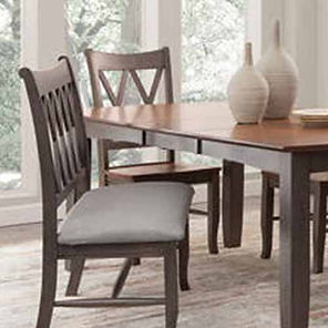 A sunlit dining room with dark finished John Thomas furniture table and side chairs.