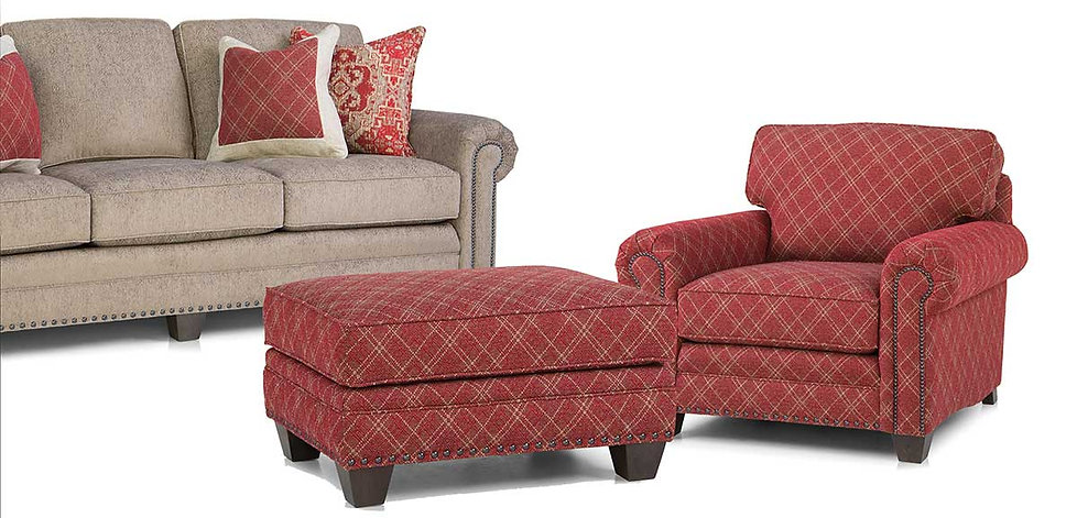 A biege Smith Brothers sofa with red print pillows and a red patterned Smith Brothers chair and ottoman.