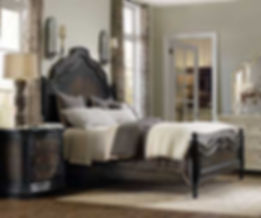 A photograph of a dark finished tuscan bedrrom suite, headboard, footboard, dresser, mirror and nightstand in a sun drenched room with a wood floor.