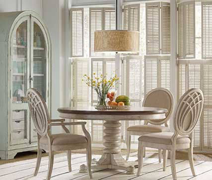 A photograph of a white cottage dining room tale and chairs ina sunny room with colorful fruit and flowers.