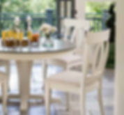 A Canadel furniture round dining table and chairs in white finish with brown top