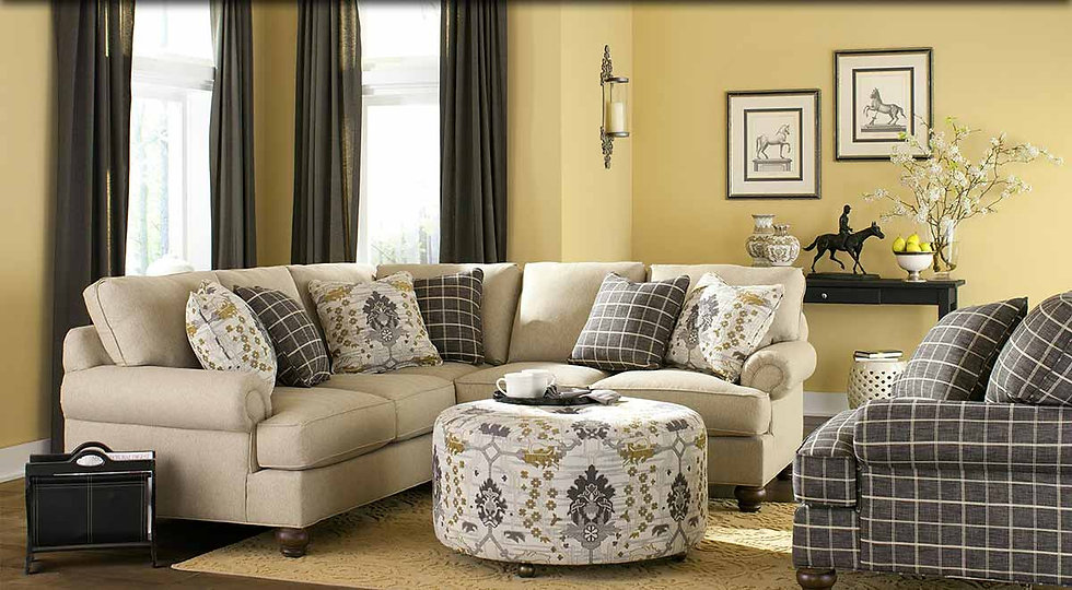 A sunlit room setting with pale yellow walls, a biege sofa sectional, gray chair and upholstered ottoman.