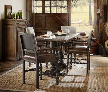 A photograph of a dark finished country dining room table and chairs in a sunny country room.