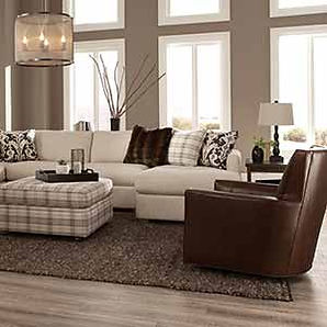 A living room scene with Craftmaster sofa, leather chair and plaid fabric ottoman.