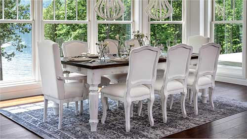 A white Canadel furniture table and chairs in an open sunlit room.