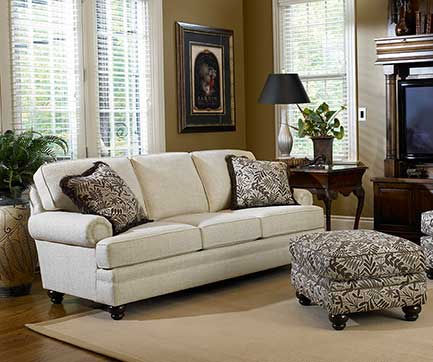 A photograph of a casual white sofa with print ottoman in a sun filled living room.