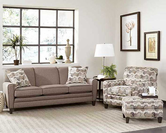 A sunlit room scene with a tan sofa and print chair and ottoman from Smith Brothers furniture