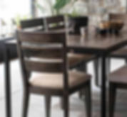 A Canadel furniture table and chairs in a dark finish with biege fabric seats