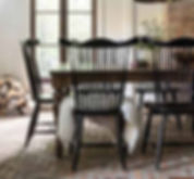 A Canadel furniture dining table and chairs with spindle backs in black finish