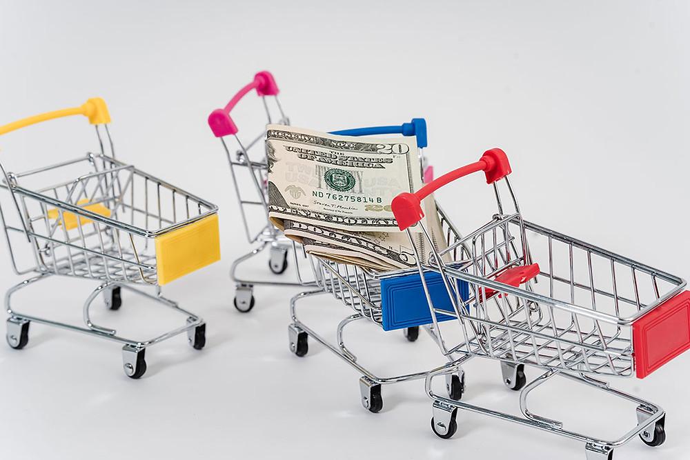 Miniature shopping cards on a white background. One cart contains cash.