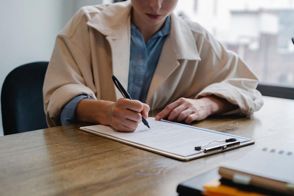 Woman filling out a paper survey.