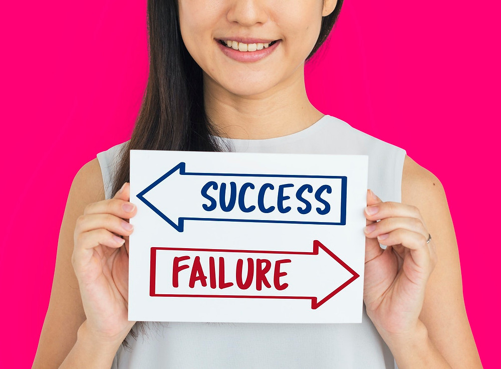 Success or failure arrows held by a woman on a pink background