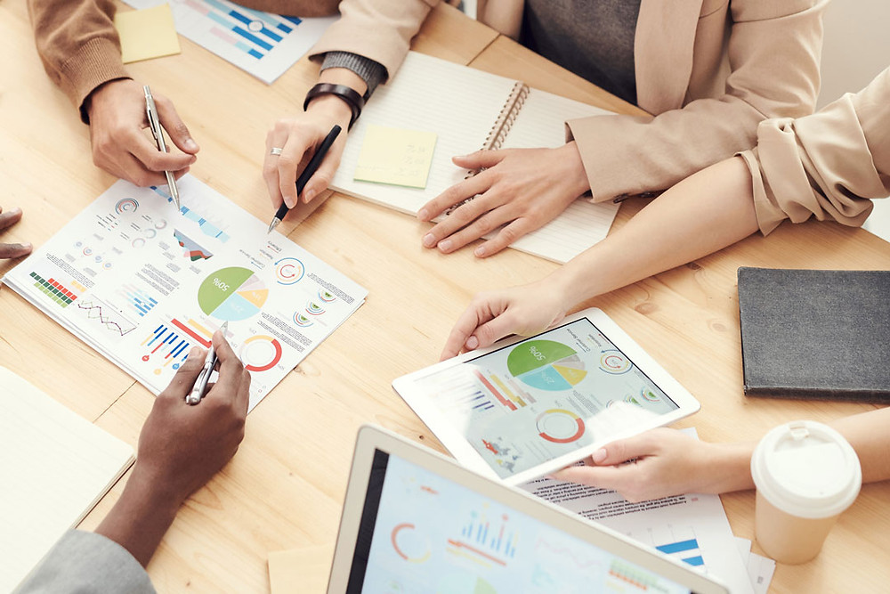 Group of people comparing charts and marketing stats on a neutral colored table.