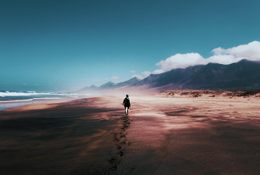 Explorer walking across a beach next to the mountains.