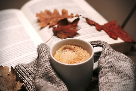 Open Bible with cup of coffee and autumn leaves