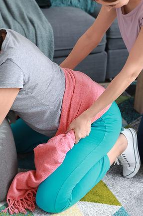 Doula massaging pregnant woman at home.j