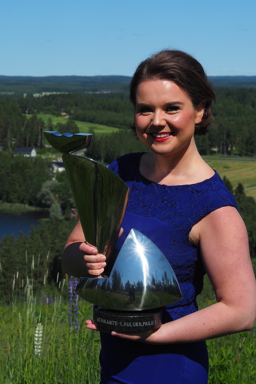 Hannakaisa Ukri Merikannon palkintoveistoksen kanssa kotimaisemissaan Viitasaarella