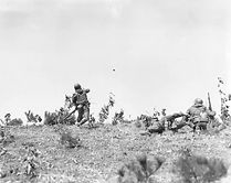 Korean conflict, 23 March 1951, platoon leader tosses a hand grenade in battle.