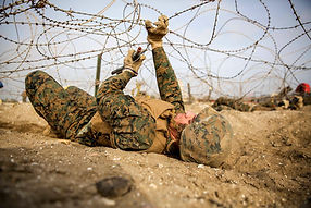 Marine escaping from the barbed wire fencing