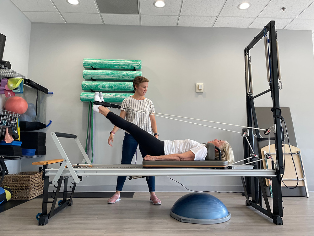 Clinical Pilates on a Pilates reformer at a physical therapy clinic.