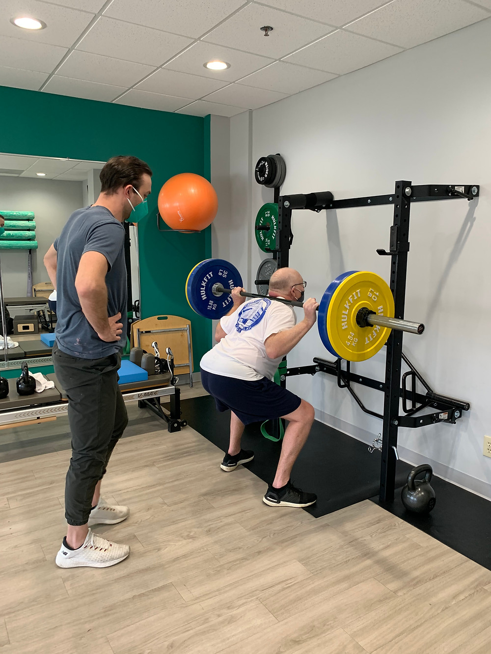 Strength Training at a squat rack in a physical therapy clinic.
