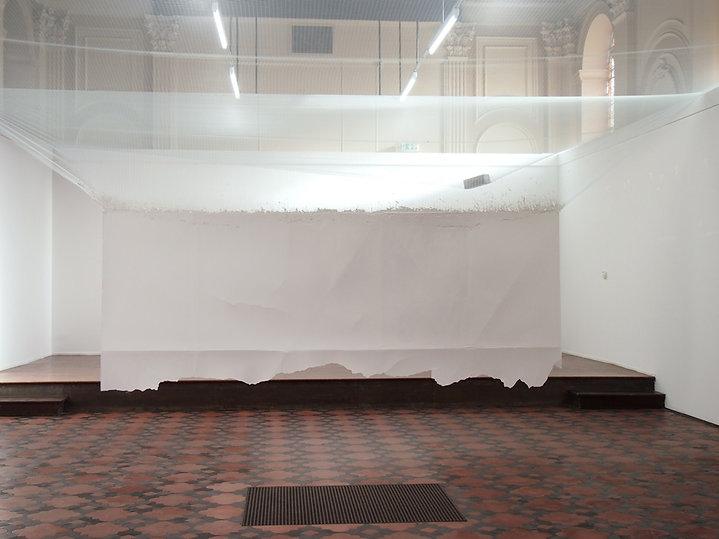 un rideau de plâtre suspendu entre les deux murs de la chapelle et au seddus une brique retenue par un filet