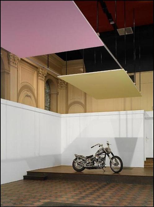 Une moto customisée à la Pollok et deux toiles accrochées sur les rampes des spots