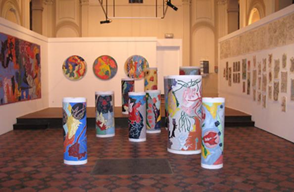 des grands dessin posés en cylindre sur le sol et des peintures accrochées aux cimaises