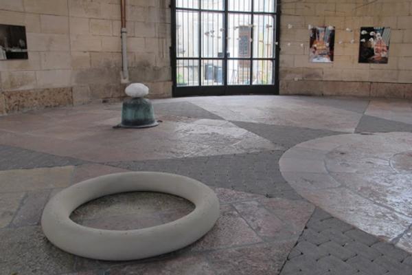 Au mur photos de Stéphane Lallemend et au sol sculptures de Jeanluc Hattemer, Le tore de révolution, support d'une danse effrénée de spermatozoïdes  « Eve II, » anneau en grès de Trier  et  « Paysage », cuivre, albâtre