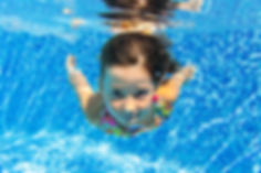 Child swims in swimming pool, playing an