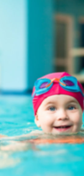 Happy little girl learning to swim with