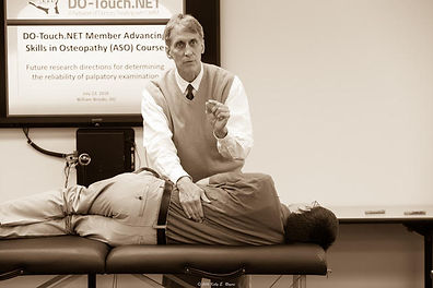 William James Brooks DO explaining hWilliam James Brooks DO explaining how to evaluate small movements on a patient's low back to his students at a conference.