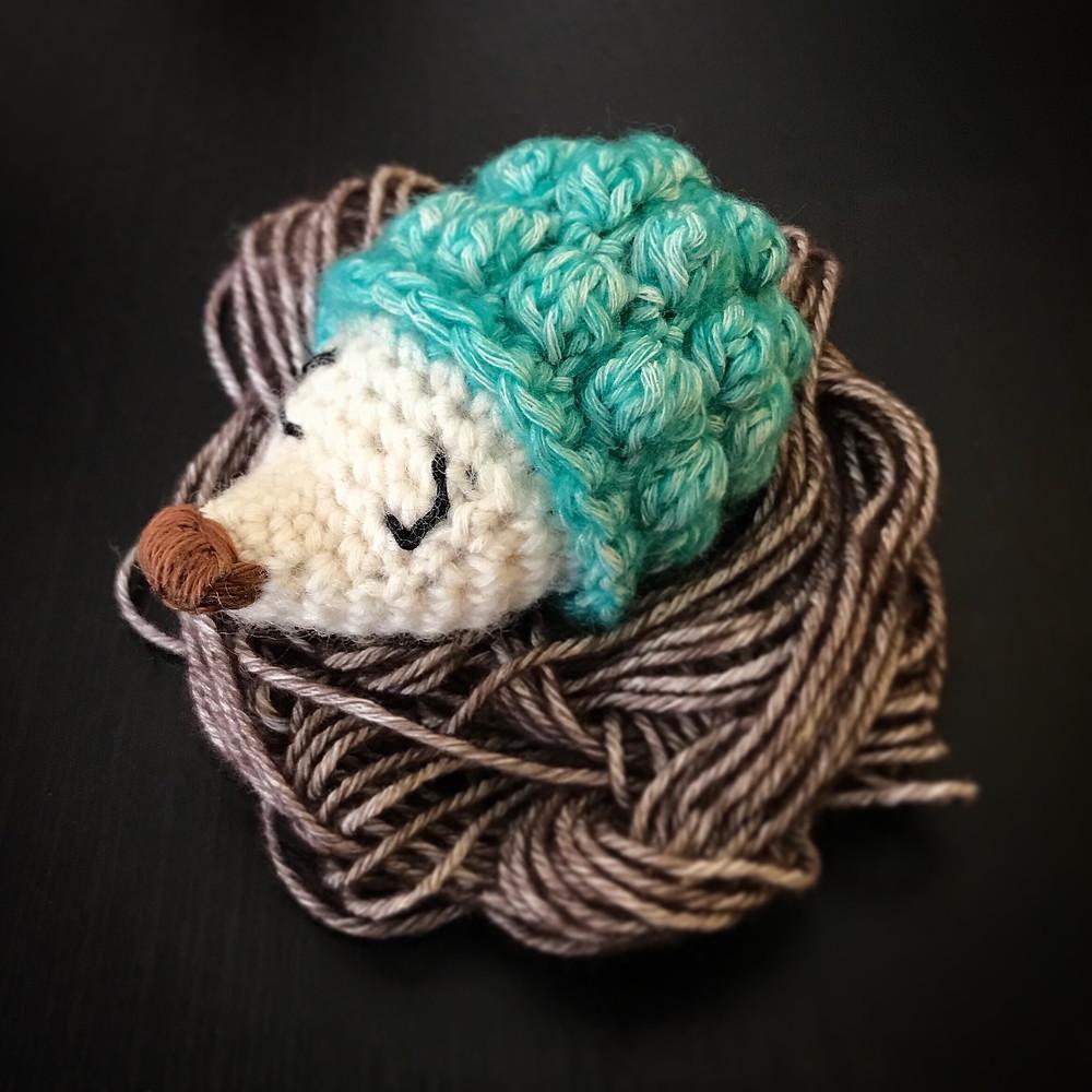 A crocheted hedgehog sleeping on a nest of yarn.