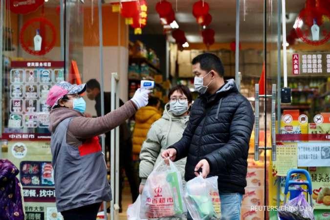 Petugas pusat penjualan menembakkan termometer untuk cek suhu sebelum memasuki area perbelanjaan