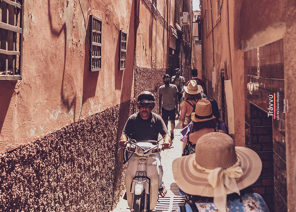 Tourists squeeze down the alleyway stepping aside to let a motorbike pass through.
