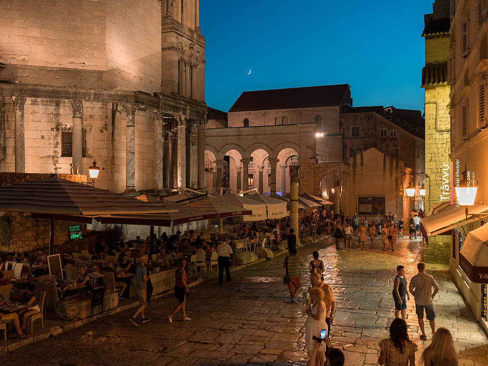 People are eating alfresco and walking around the shiny cobbled streets of Split Old Town