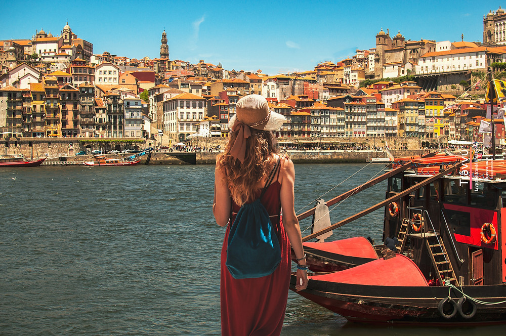 A young woman in a long red dress and sun hat is about to board a traditional boat the Douro River in Porto.