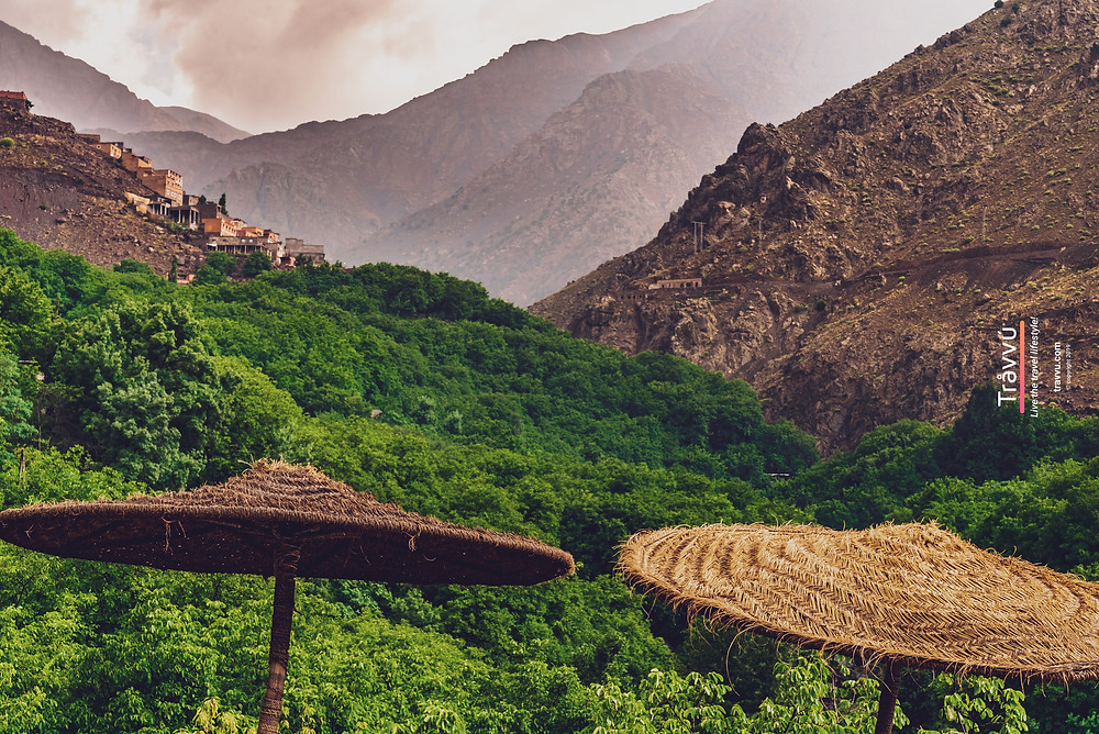 A rocky but humid mountain range with two of the riad's hay umbrellas in view.
