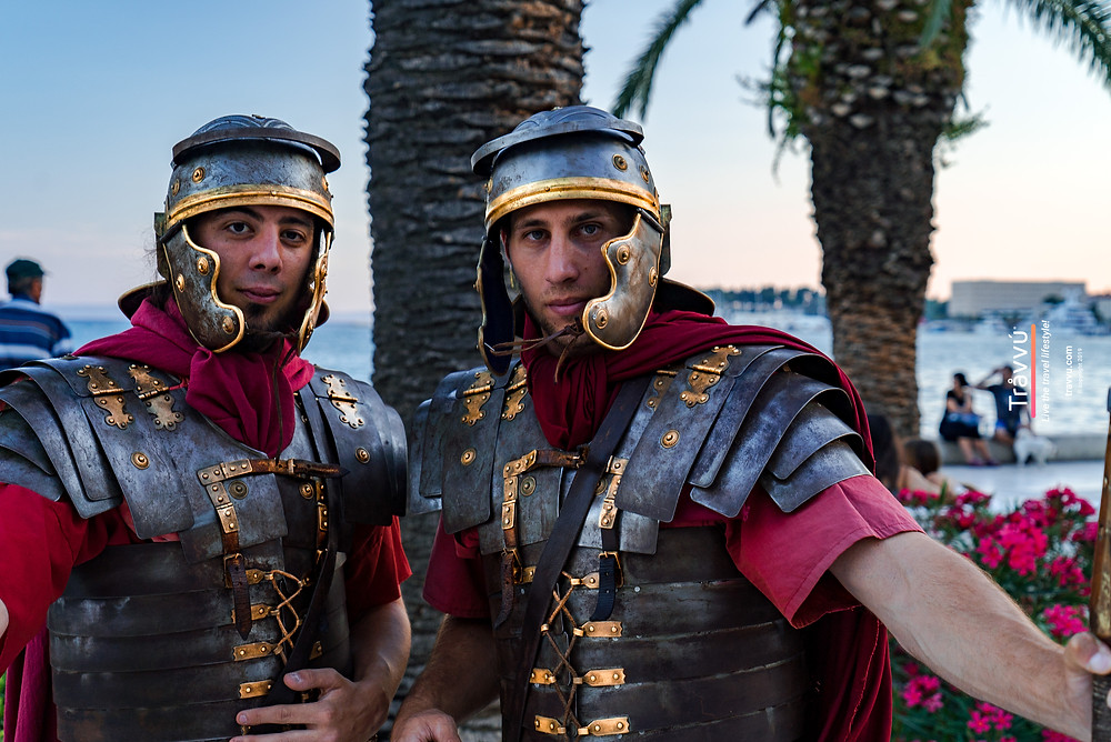 Two men dressed in old fashioned roman soldier uniforms pose for a picture. Crowned with metal helmets and wrapped in red cloth.