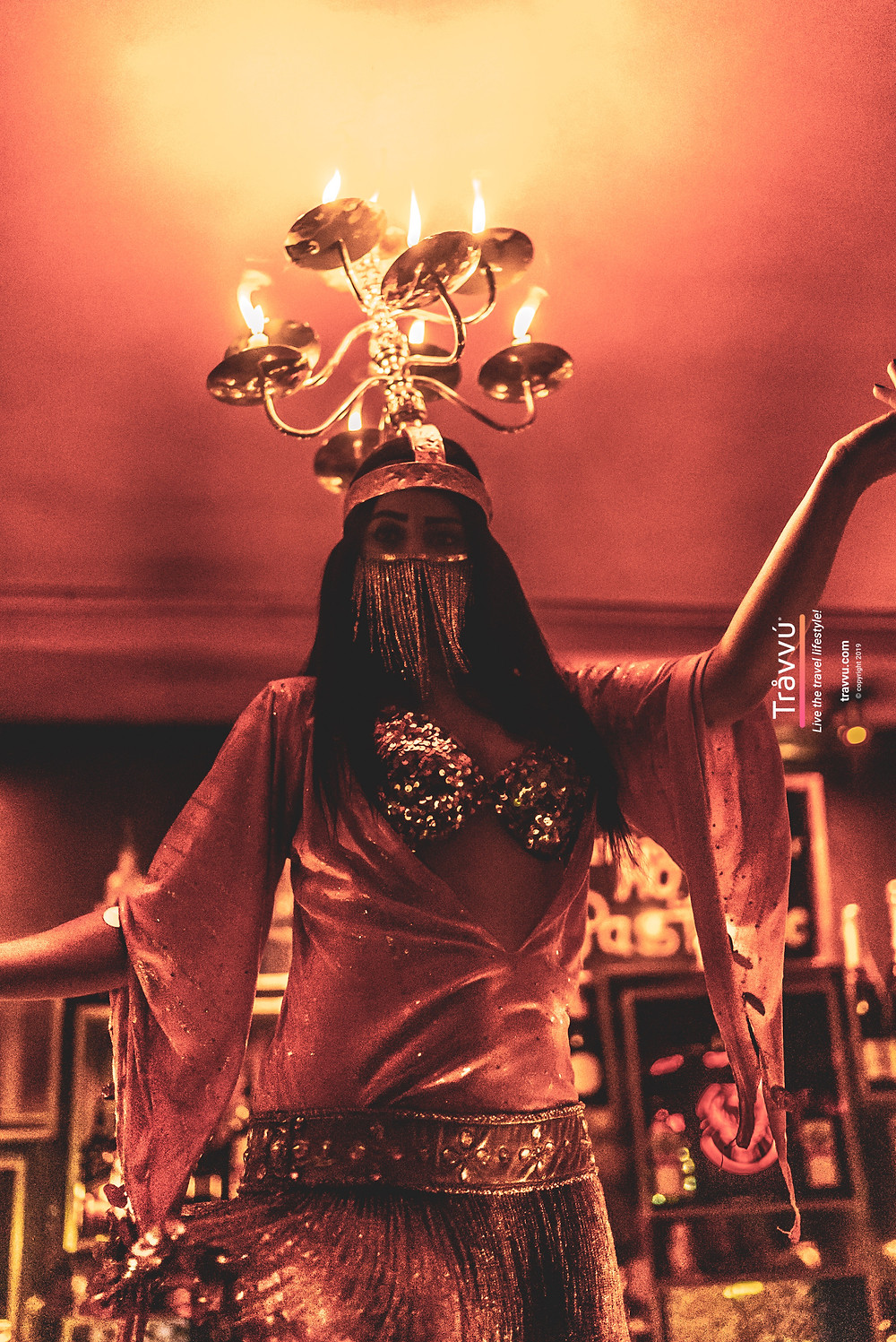 A belly dancer balances candles on her head as she dances around the diners tables.