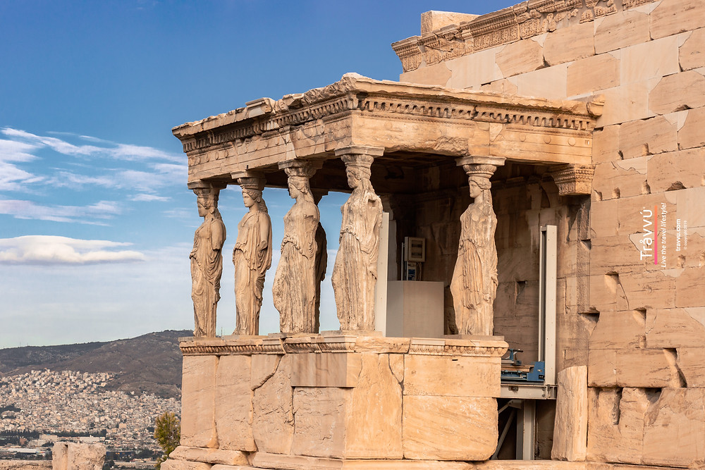 Temple Of Athena Nike with 6 pillars made of sculptured women dressed in traditional robes with the backdrop of a sunny Athens city.
